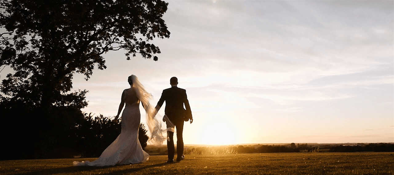 Wedding Videography - Couple Strolling Into Sunset